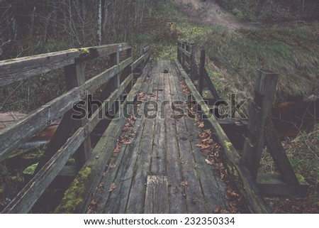 old wooden bridge over small river. autumn.. Vintage effect. - stock photo