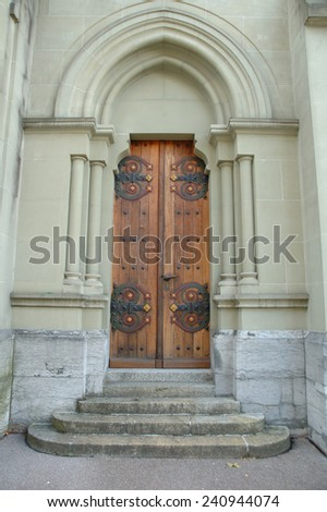 Old wooden brown church door and stone stairs