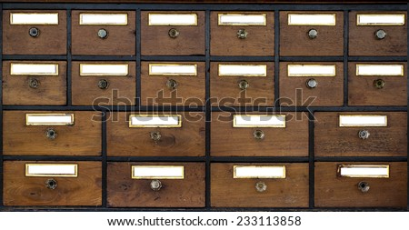 Old wooden cabinet of rows of drawers with vintage labels.