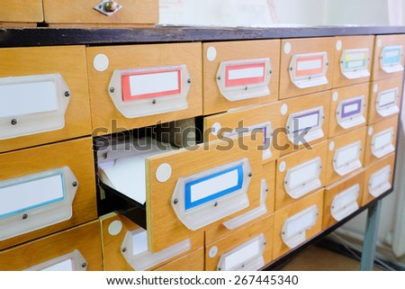 Old wooden card catalog with one opened drawer in library - stock photo