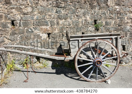Old wooden carriage on the ground and stone wall at background.