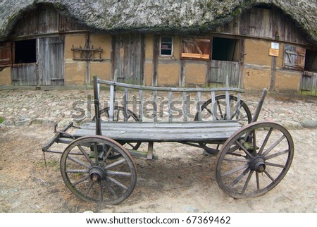 Old wooden cart at front of stable witch thatched roof