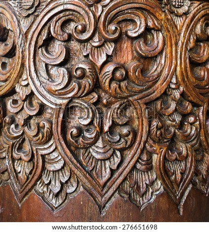 Old wooden carving on the pillar of Thai temple - stock photo