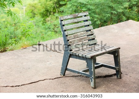 Old wooden chair on broken cement floor on green mountains range background