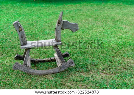 Old wooden chair on green grass texture - stock photo