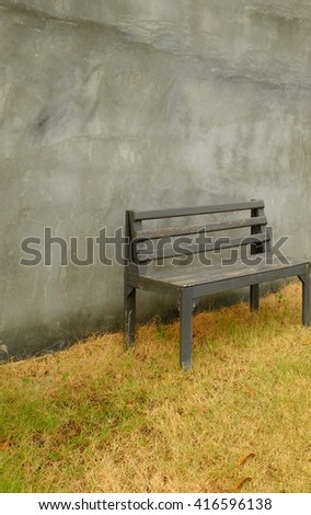Old wooden chair on the grass field reverses, with bare concrete walls.