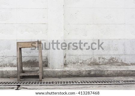 old wooden chair with dirty grungy wall - stock photo