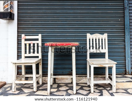 Old wooden chairs and table in front of the steel shutter door. - stock photo