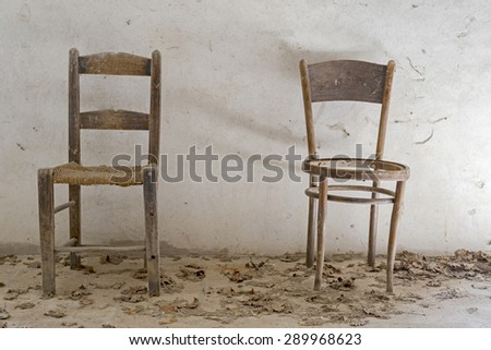 old wooden chairs on white background,dust and cobwebs on the chairs natural light, front view
