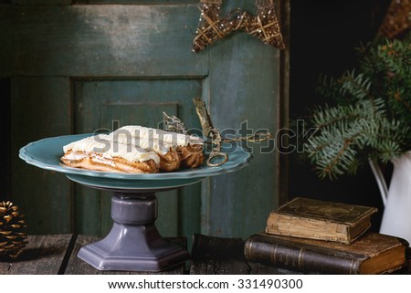 Old wooden Christmas table with big plate of Butter cream Eclairs, decorating by Christmas stars, tree and vintage books. With open old door at bachground. Dark rustic style, outside view - stock photo