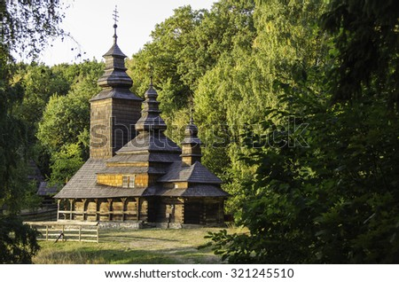 Old wooden church. In a clearing among the trees and bushes.