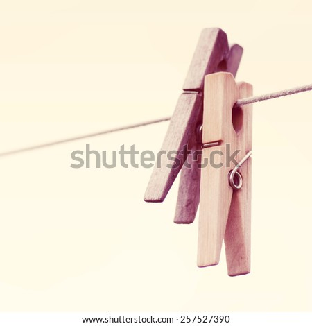 Old wooden clothespin hanging on rope, depth of field.Special toned photo in vintage style - stock photo