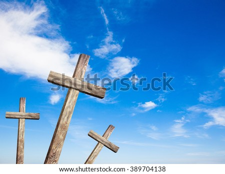 Old wooden cross on blue sky background