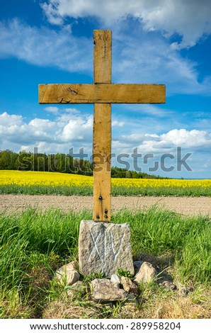 Old wooden cross on the large field