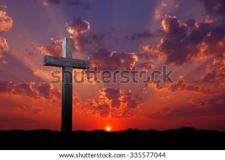 Old wooden cross over red and purple sunrise or sunset  - stock photo