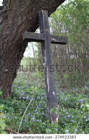 Old wooden cross under the tree