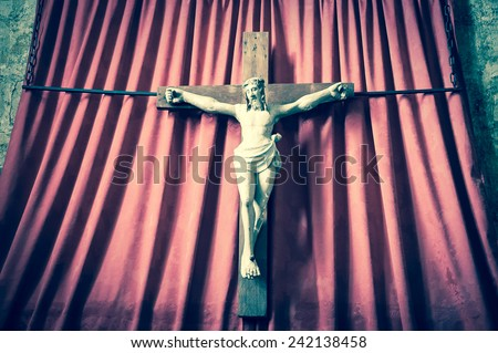 Old wooden crucifix of Jesus Christ isolated on drapery background in medieval church. Aged photo. - stock photo