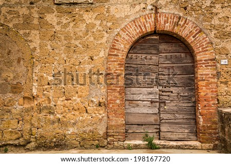 Old wooden door and brick wall - stock photo