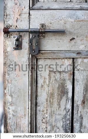 Old, wooden door and metallic lock - stock photo