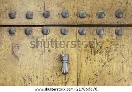 Old wooden door, detail of a door knocker - stock photo