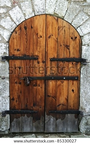 Old wooden door in a stone wall. - stock photo