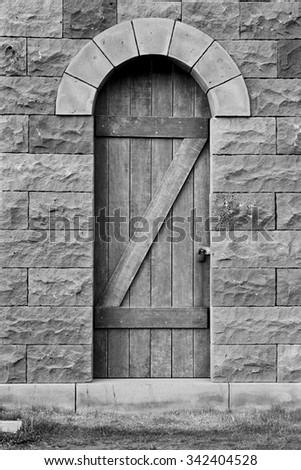 Old wooden door in a stone wall in black and white - stock photo