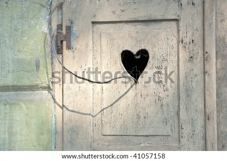old wooden door in meran, Tirol, Italy with a carved romantic heart