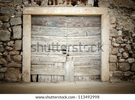 Old wooden door in stone house, Croatia - stock photo
