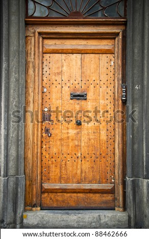 Old wooden door in the town of Mons. Belgium. Fragment, close-up.
