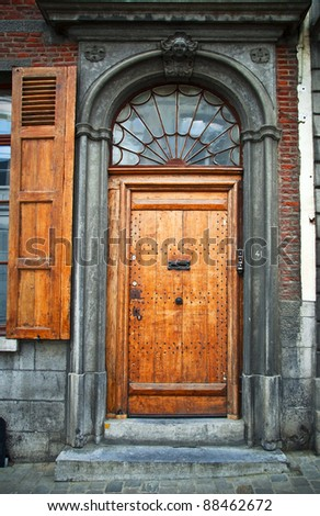 Old wooden door in the town of Mons. Belgium. Fragment, close-up. - stock photo