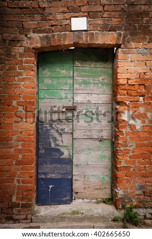 Old wooden door locked with peeling paint in red brick wall