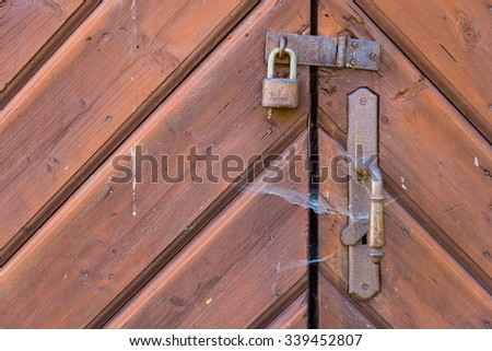 Old wooden door of the antique house closed with chains and padlock.