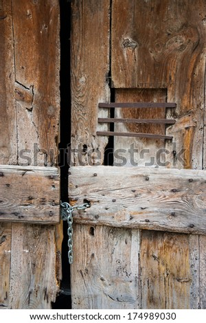 Old wooden door of the antique house closed with chains and padlock. Closeup.