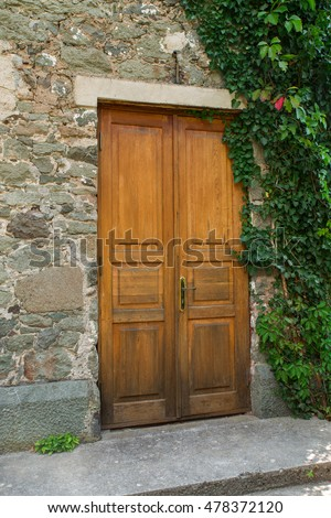 Old wooden door of the house, overgrown with ivy
