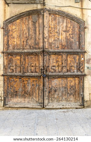 Old wooden door on a background of the facade - stock photo