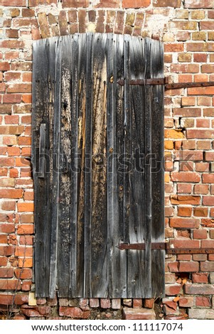 Old wooden door on a brick wall - stock photo