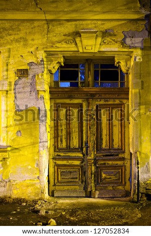 Old wooden door on abandoned yellow house - stock photo