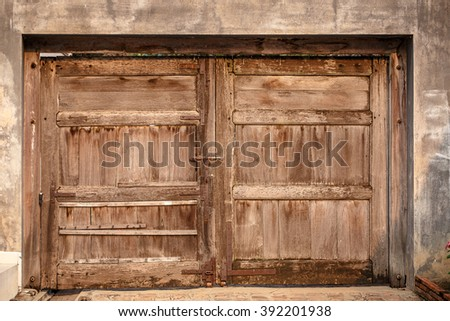 Old wooden door on the wall - stock photo