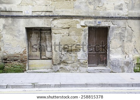 Old wooden door wall, detail of a building in ruins and abandoned - stock photo