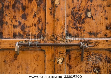 Old wooden door  with a padlock and an oxidized latch
