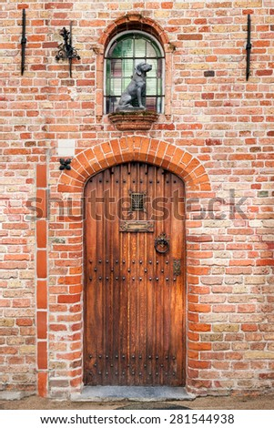 old wooden door with a sculpture of a dog, the facade of a house in the city of Bruges, Belgium - stock photo