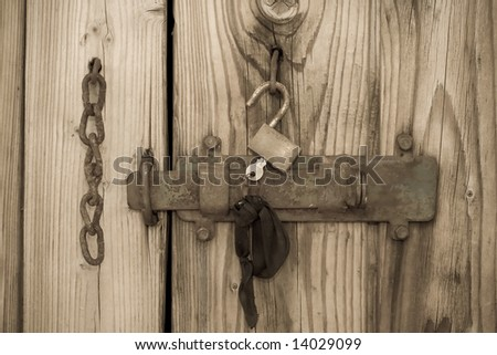 Old wooden door with a vintage lock. - stock photo