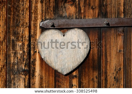 Old wooden door with an empty sign that looks like a heart - stock photo