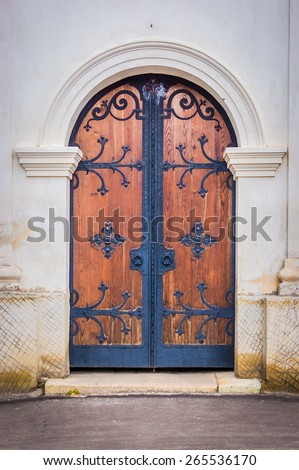 Old wooden door with forged elements  - stock photo