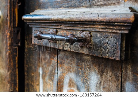 Old wooden door with forged iron ornament - stock photo
