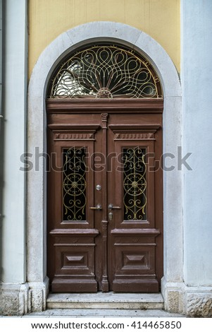 Old wooden door with glass inserts in the ancient beautiful building in Western Europe. - stock photo