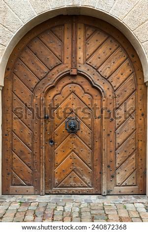 Old wooden door with  lion head  knocker - stock photo