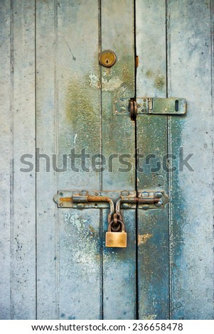 old wooden door with many rusty locks