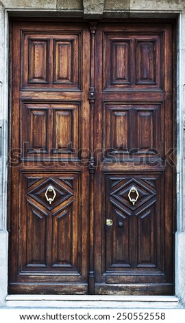 Old wooden door with metal knocker - stock photo