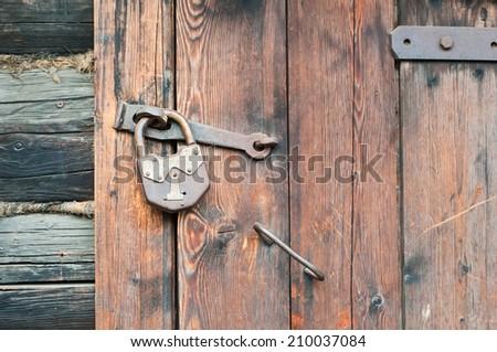 Old wooden door with metallic doorlock - stock photo